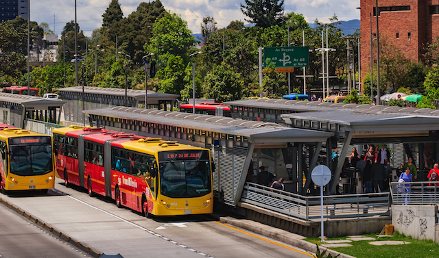 Bogot?, Colombia - September 22, 2015: The Salitre El Greco TransMilenio station on Avenida El Dorado that runs from the East of the capital City, to the West; from downtown Bogot?, to the International Airport. The two articulated busses on the lower section of the photo are coming from the Airport side and going to the centre of the city. People can be seen getting off from the busses and leaving the station. In the far background, the always present Andes mountains can be seen. Photo shot in the afternoon sunlight; horizontal format.