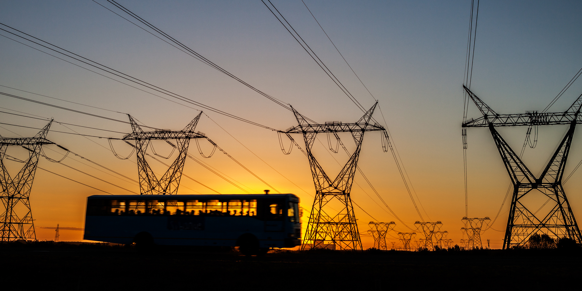 Bus with passengers driving by power lines in South Africa at sunset.